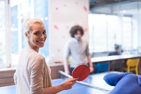 gruppo di giovani imprenditori che giocano a ping pong presso l'ufficio creativo moderno