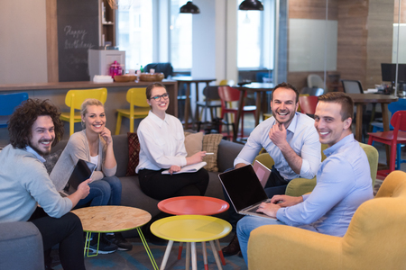 Group of a young business people discussing business plan at modern startup office building Imagens