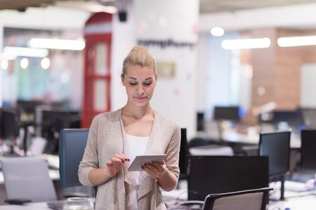 Jolie femme d'affaires utilisant la tablette devant le démarrage Office Interior Banque d'images - 89903166