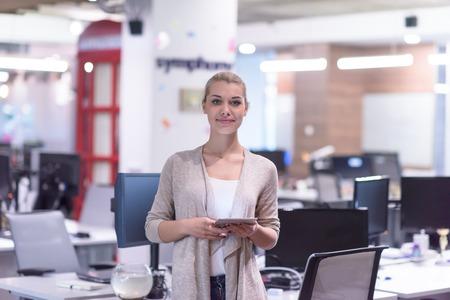 Jolie femme d'affaires utilisant la tablette devant le démarrage Office Interior Banque d'images - 89467717