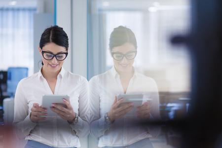 Jolie femme d'affaires utilisant la tablette devant le démarrage Office Interior Banque d'images - 89467838