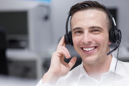 Jonge lachende mannelijke call center operator doet zijn werk met een headset Stockfoto