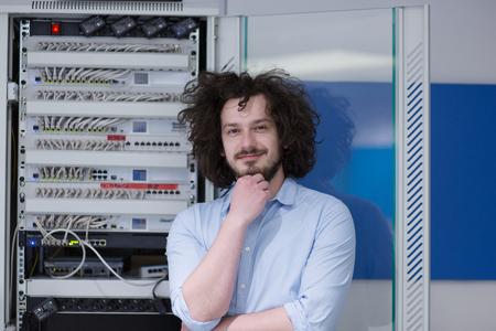 portrait of young handsome business man engeneer in datacenter server room