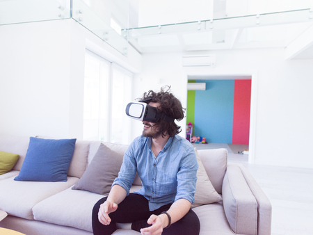 95e7861ac825 happy man getting experience using VR-headset glasses of virtual reality at  home Stock Photo