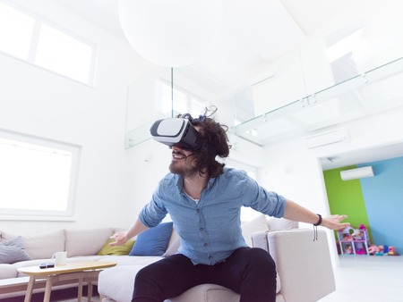 virtual reality simulator: happy man getting experience using VR-headset glasses of virtual reality at home Stock Photo