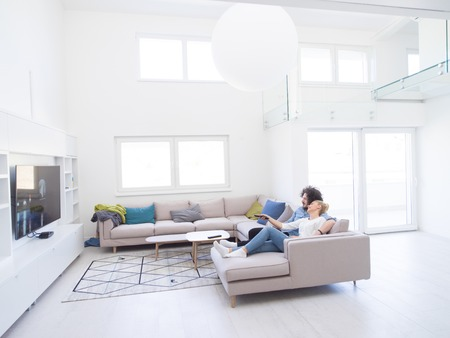 Young couple on the sofa watching television together in their luxury home Stockfoto