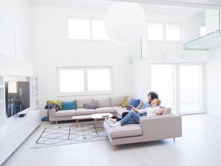 Młoda para na kanapie przed telewizorem w swoim luksusowym domu