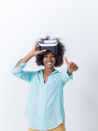 virtual reality simulator: Happy african american girl getting experience using VR headset glasses of virtual reality, isolated on white background Stock Photo