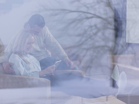 Young Couple in front of fireplace surfing internet using digital tablet on cold winter day at home Stock Photo