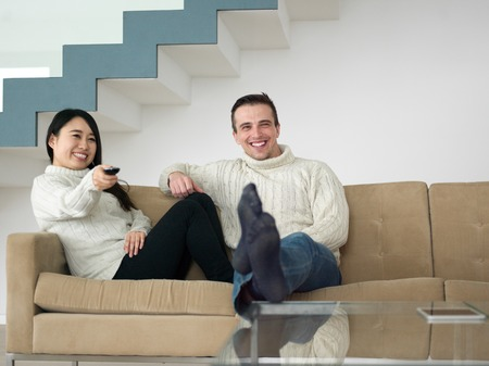 Young multiethnic couple on the sofa watching television together at luxury home Stock Photo