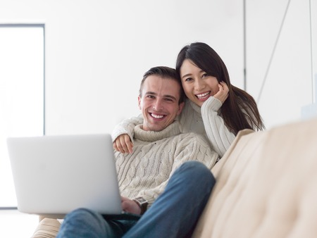 Young multiethnic couple relaxing at luxury home using laptop computer reading in the living room on the sofa couch. Фото со стока