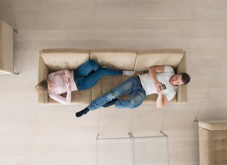 top view of Young couple on sofa using a mobile phones Stock Photo