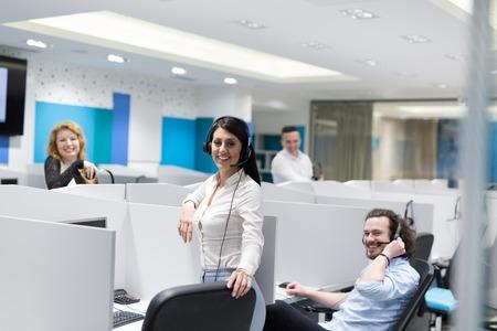 Een groep jonge bedrijfsmensen met hoofdtelefoon die en steun aan klanten in een call centrebureau werken geven Stockfoto
