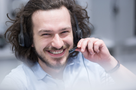 young smiling male call centre operator doing his job with a headset Stock Photo