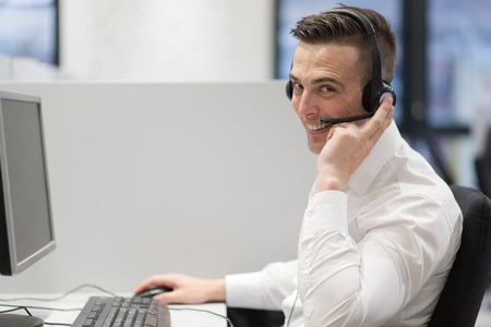 A young smiling male call centre operator doing his job with a headset Stock Photo