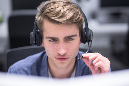 young smiling male call centre operator doing his job with a headset Imagens