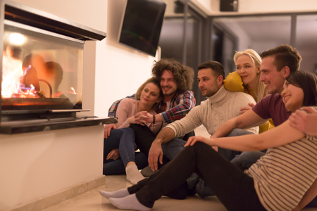group of young multiethnic couples sitting on the floor in front of fireplace at cold winter night Stock Photo