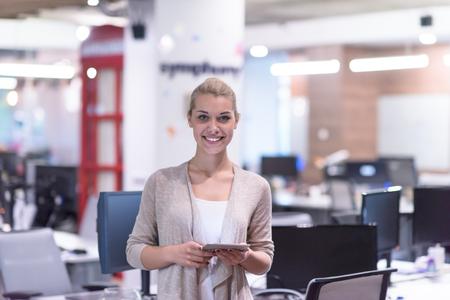 Jolie femme d'affaires utilisant la tablette devant le démarrage Office Interior Banque d'images - 89920839