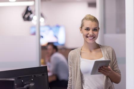 Jolie femme d'affaires utilisant la tablette devant le démarrage Office Interior Banque d'images - 89941363