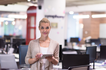 Pretty Businesswoman Using Tablet In front of startup Office Interior