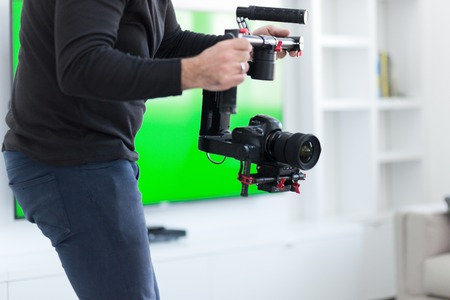 young videographer with gimball video slr at work