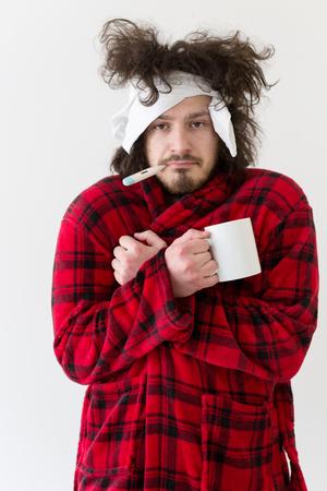 jonge man met griep en koorts gewikkeld bedrijf kopje helende thee geïsoleerd over wit