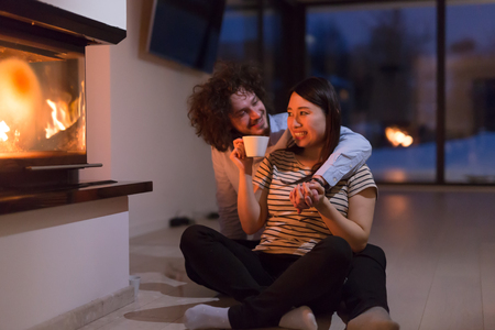 Young romantic multiethnic couple sitting on the floor in front of fireplace at home, talking and drinking tea on cold winter night 免版税图像