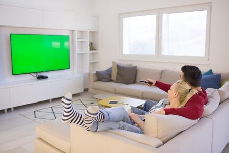 Jong koppel op de bank tv-kijken samen in hun luxe huis Stockfoto