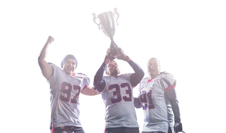 happy american football team with trophy celebrating victory isolated on white background