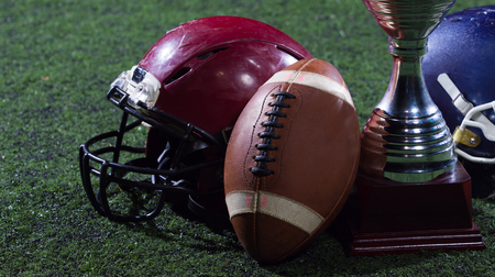 closeup shot of american football,helmets and trophy on grass field at night