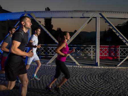 도시 스포츠, 밤에 이른 아침에 도시에서 다리를 건너 조깅 건강 한 젊은이의 그룹 스톡 콘텐츠