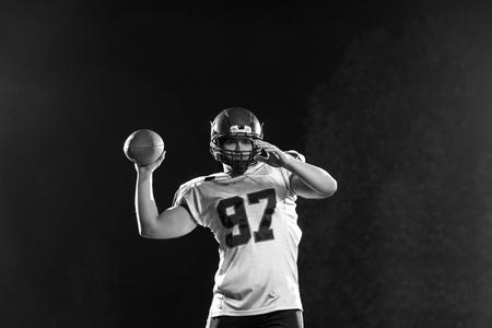 黒い背景にラグビーボールを投げるアメリカンフットボール選手