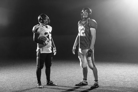 portrait of confident American football players holding ball while standing on field at night Stock Photo