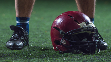 closeup shot of american football player and helmet on grass field at night