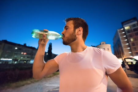 young athletic man drinking water after a night running session in the city Banco de Imagens