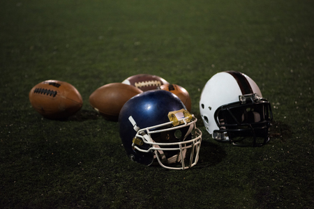 american football and helmets on grass field at night