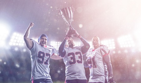 happy american football team with trophy celebrating victory in the cup final on big modern stadium with lights and flares at night