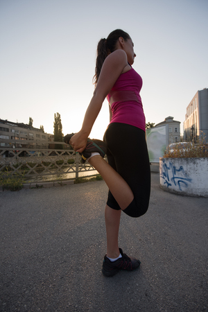 athlete woman warming up and stretching while preparing for running on the city street at  sunny morning