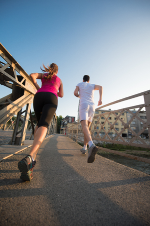 urban sports, healthy young couple jogging across the bridge in the city at sunny morning Stock Photo