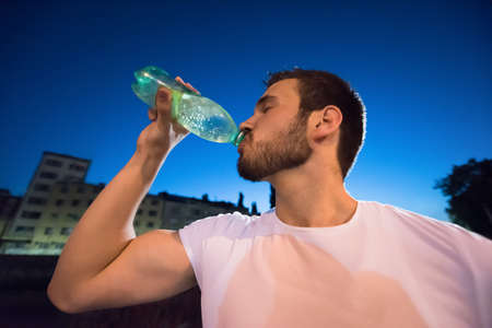 young athletic man drinking water after a night running session in the city Stok Fotoğraf