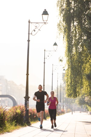 urban sports, healthy young couple jogging  in the city at sunny morning Stock Photo