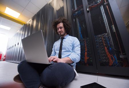 Mężczyzna informatyk pracuje na laptopie w serwerowni w nowoczesnym centrum danych Zdjęcie Seryjne