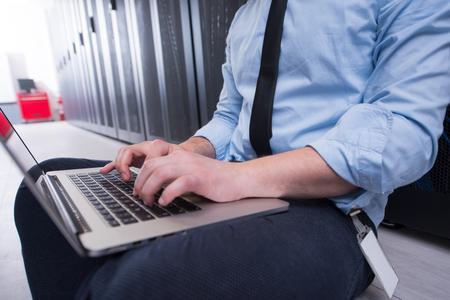 ingénieur mâle travaille sur un ordinateur portable dans la salle serveur dans le centre de données numériques Banque d'images