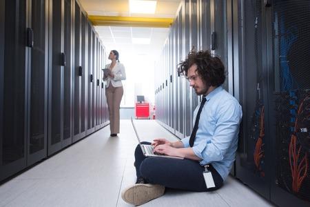 랩톱 및 태블릿 컴퓨터를 사용하여 데이터 센터의 서버에서 함께 작업하는 젊은 기술자 팀 스톡 콘텐츠