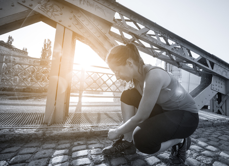 woman tying running shoes laces getting ready to run on city at sunny morning Stok Fotoğraf