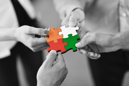 Group of business people assembling jigsaw puzzle and represent team support and help concept Banco de Imagens - 94128748