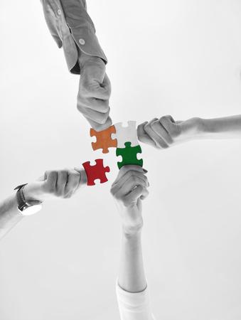 Grupa ludzi biznesu układająca puzzle i reprezentująca koncepcję wsparcia zespołu i pomocy