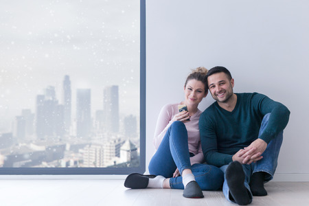 happy young couple sitting near window at home on cold winter day Stock Photo