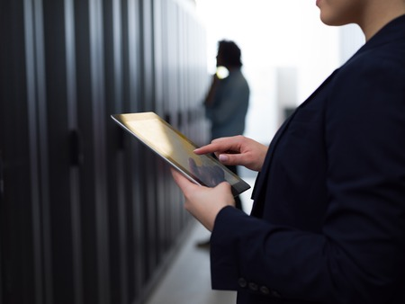 Female IT engineer working on a tablet computer in server room at modern data center Stock Photo