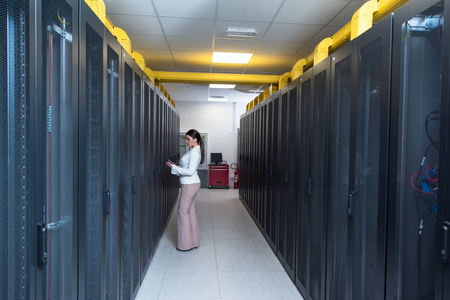 Female IT engineer working on a tablet computer in server room at modern data center 스톡 콘텐츠